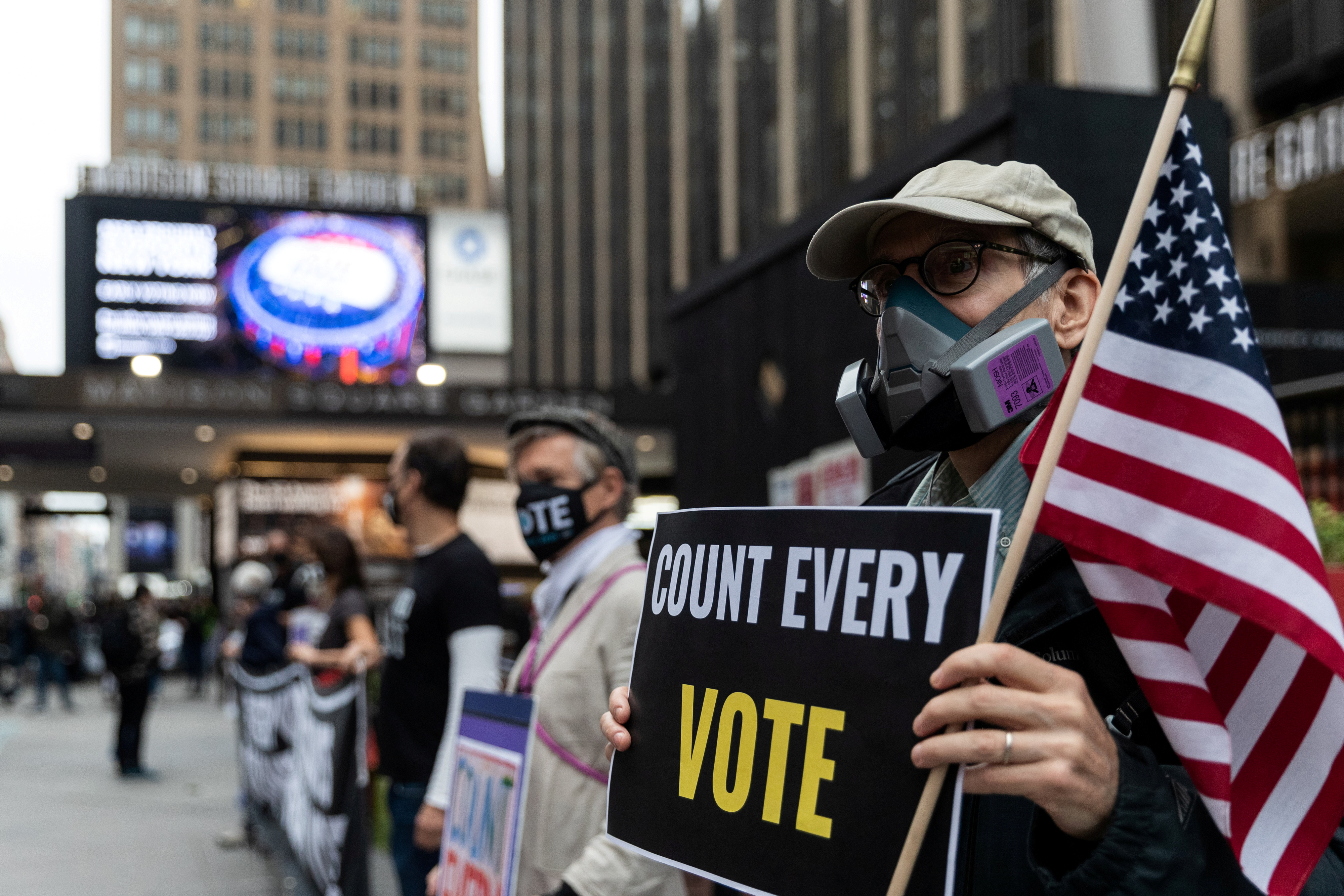 An older man wearing a respirator-style protective mask due to COVID-19 pandemic holds a sign outside Madison Square Garden, which is used as a polling station, on the first day of early voting in Manhattan, New York.