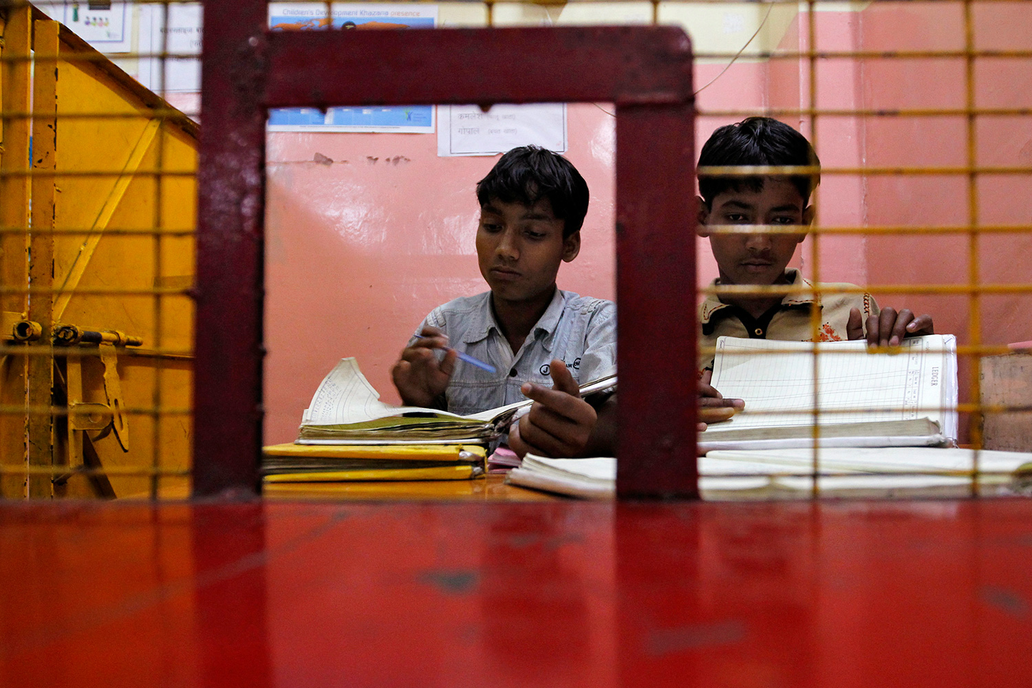 The photo shows two children behind a cashier's window looking through stacks of paper.