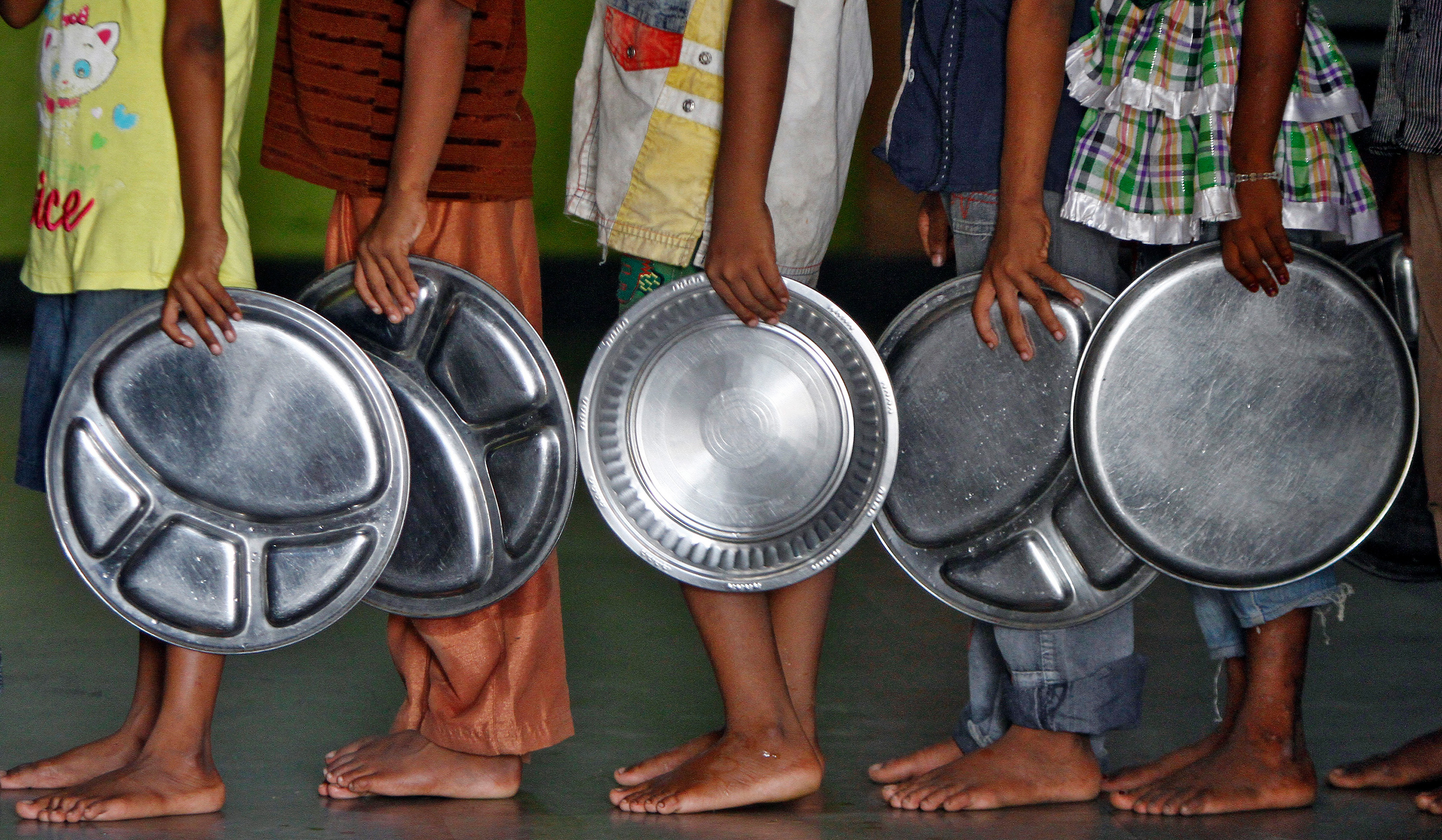The photo shows a long line of people holding large metal platters.