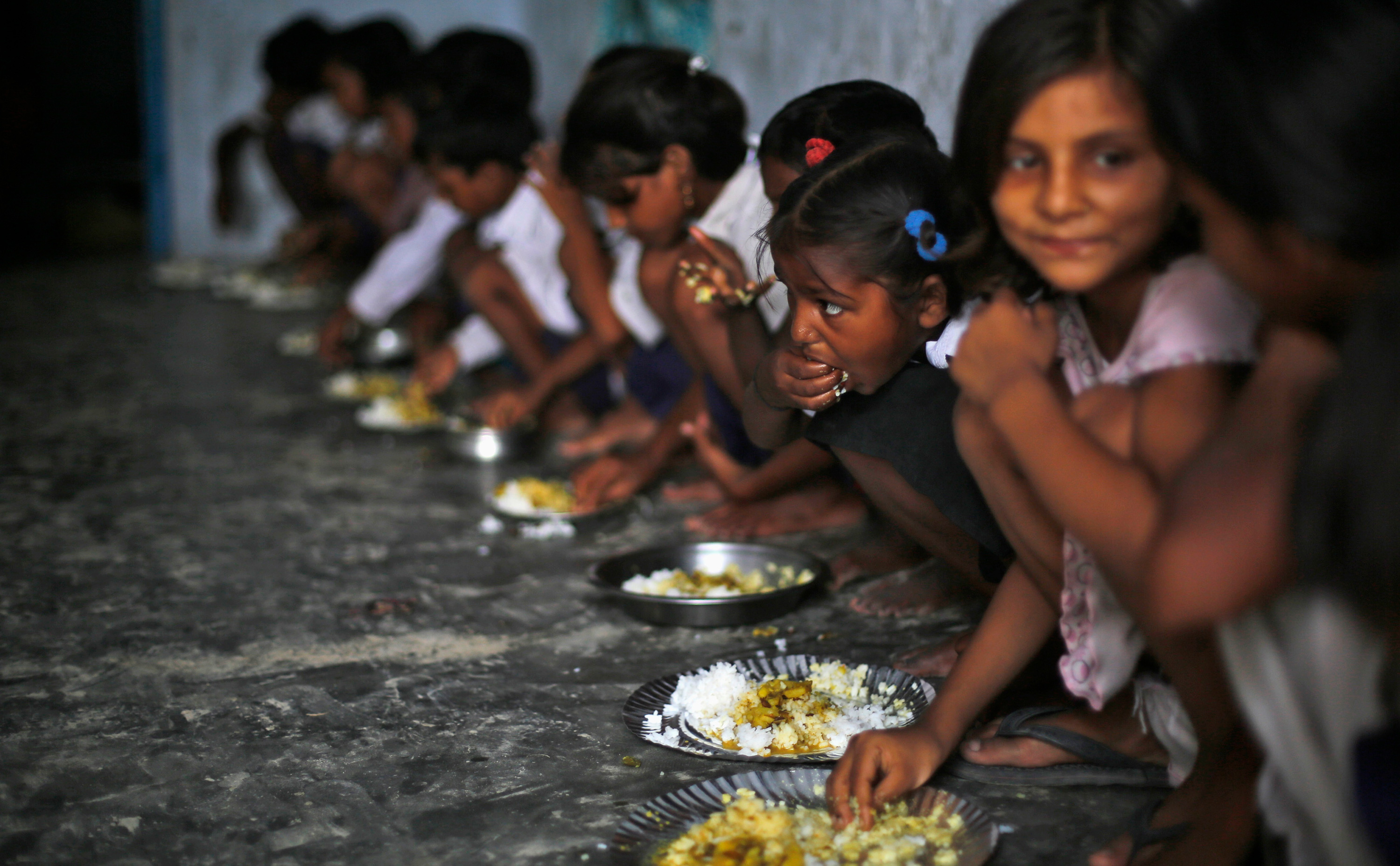 The photo shows a class of young children lined up against a wall, seated, and eating plates of rice and curry with their hands.