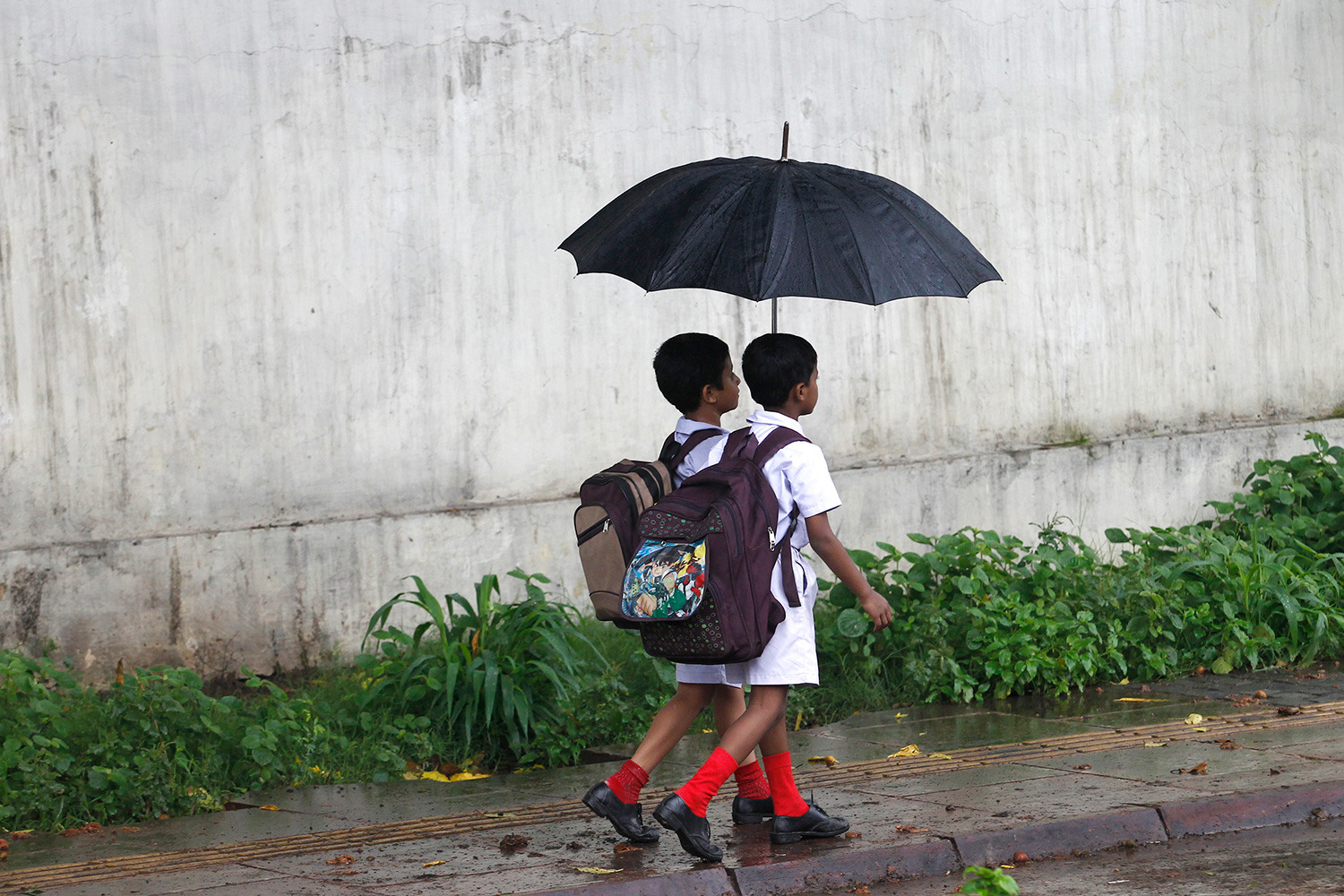The photo shows two small children with umbrellas walking through the rain.