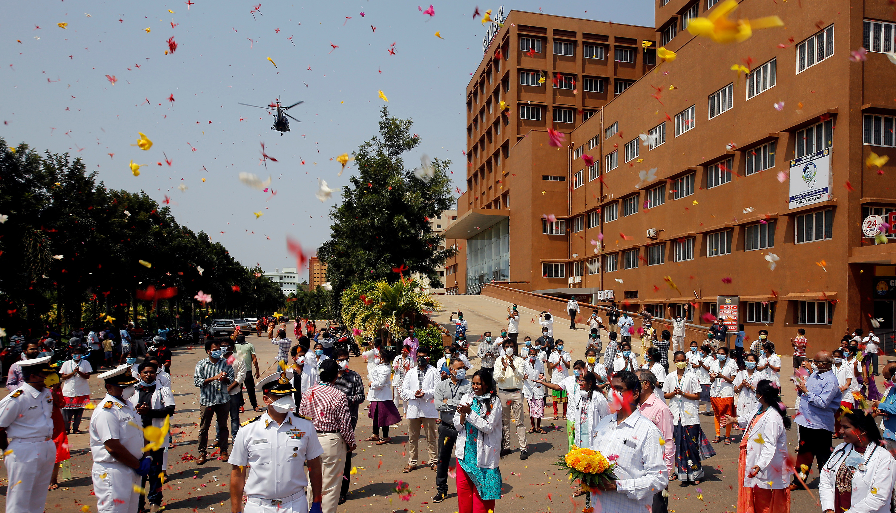 The photo shows a large brick hospital with lots of health workers and some uniformed naval officers out front as a shower of flower pedals rains down on them from above.