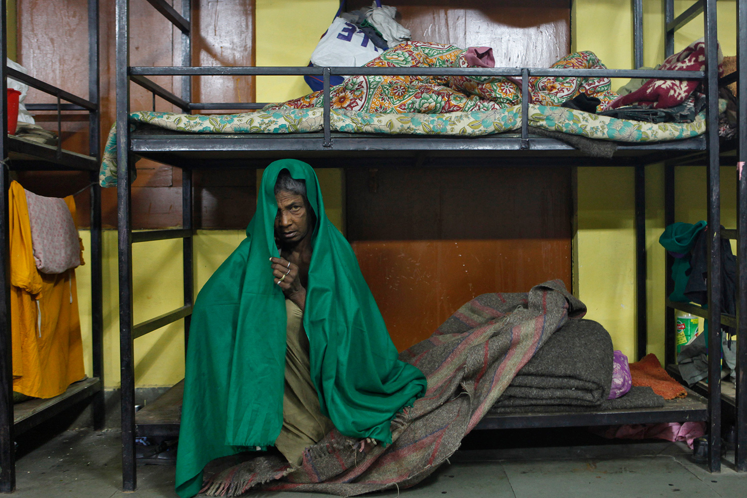 Picture shows a woman sitting on a bunk while wrapped in a bright green blanket.