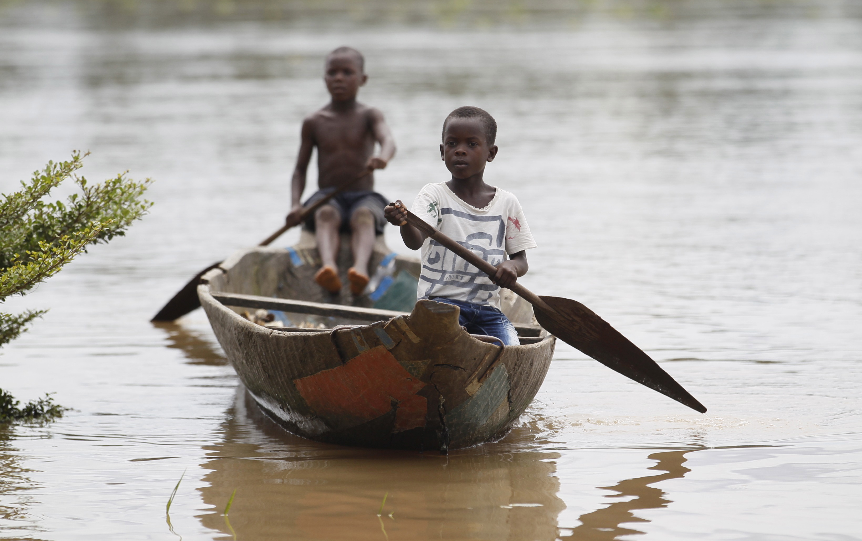 Two young boys paddle a canoe near the shore of the Nun River in Yeneka village in Nigeria's Bayelsa state on October 8, 2015.