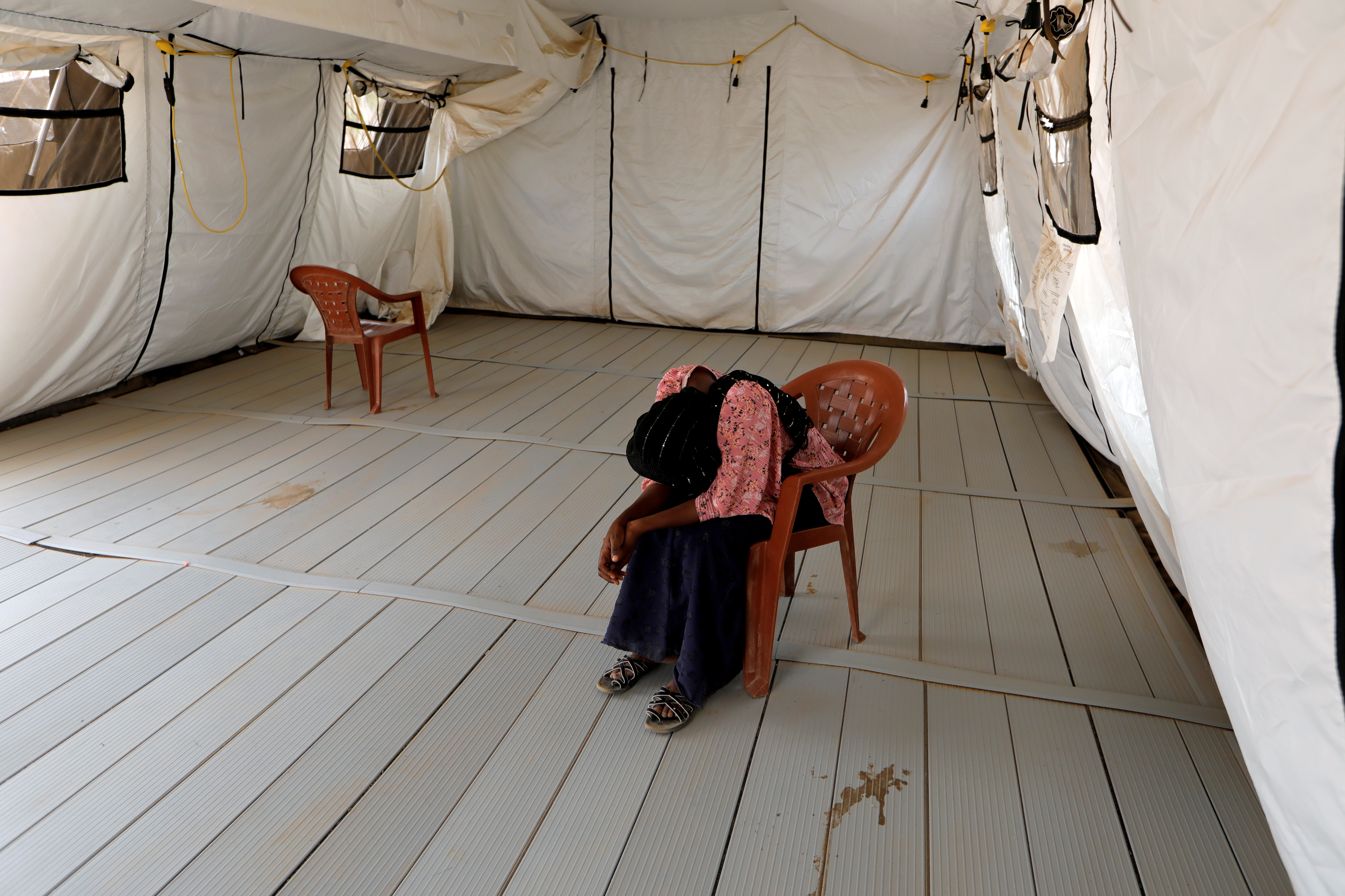 A local resident waits to be examined after she was isolated due to the symptoms of the coronavirus disease (COVID-19), inside an isolation tent for suspected cases at the army field hospital in Touba, Senegal May 1, 2020.