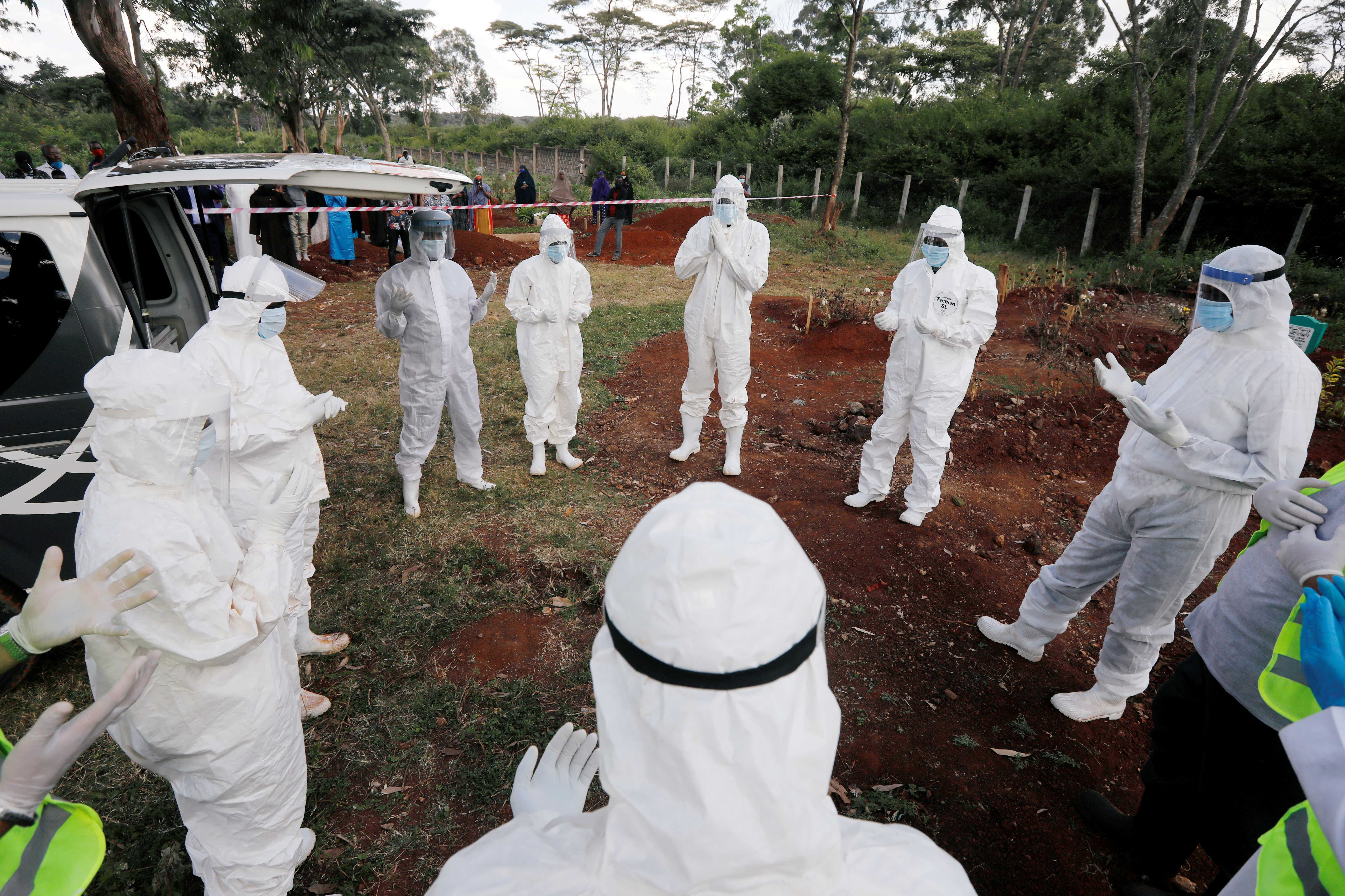 Volunteers from the National Muslim COVID-19 Response Committee, wearing Personal Protective Equipment (PPE), pray before the burial of Abdullahi Adan, 52, who died due to the coronavirus disease (COVID-19), at the separated section of the muslim cemetery in Nairobi, Kenya August 6, 2020.