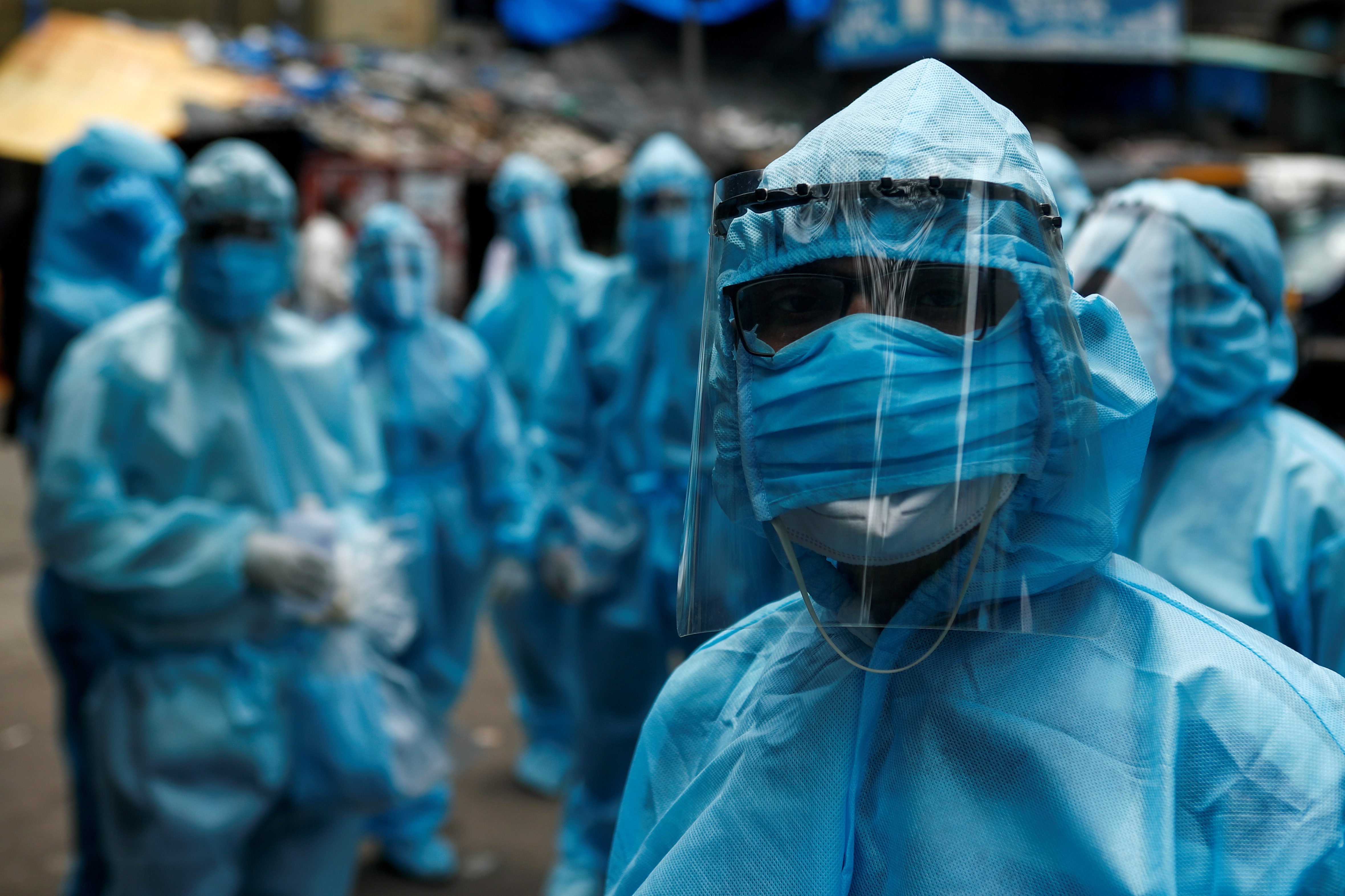Health-care workers wait to take off their personal protective equipment after the end of a check-up camp for the COVID-19) at a slum in Mumbai, India on June 14, 2020.