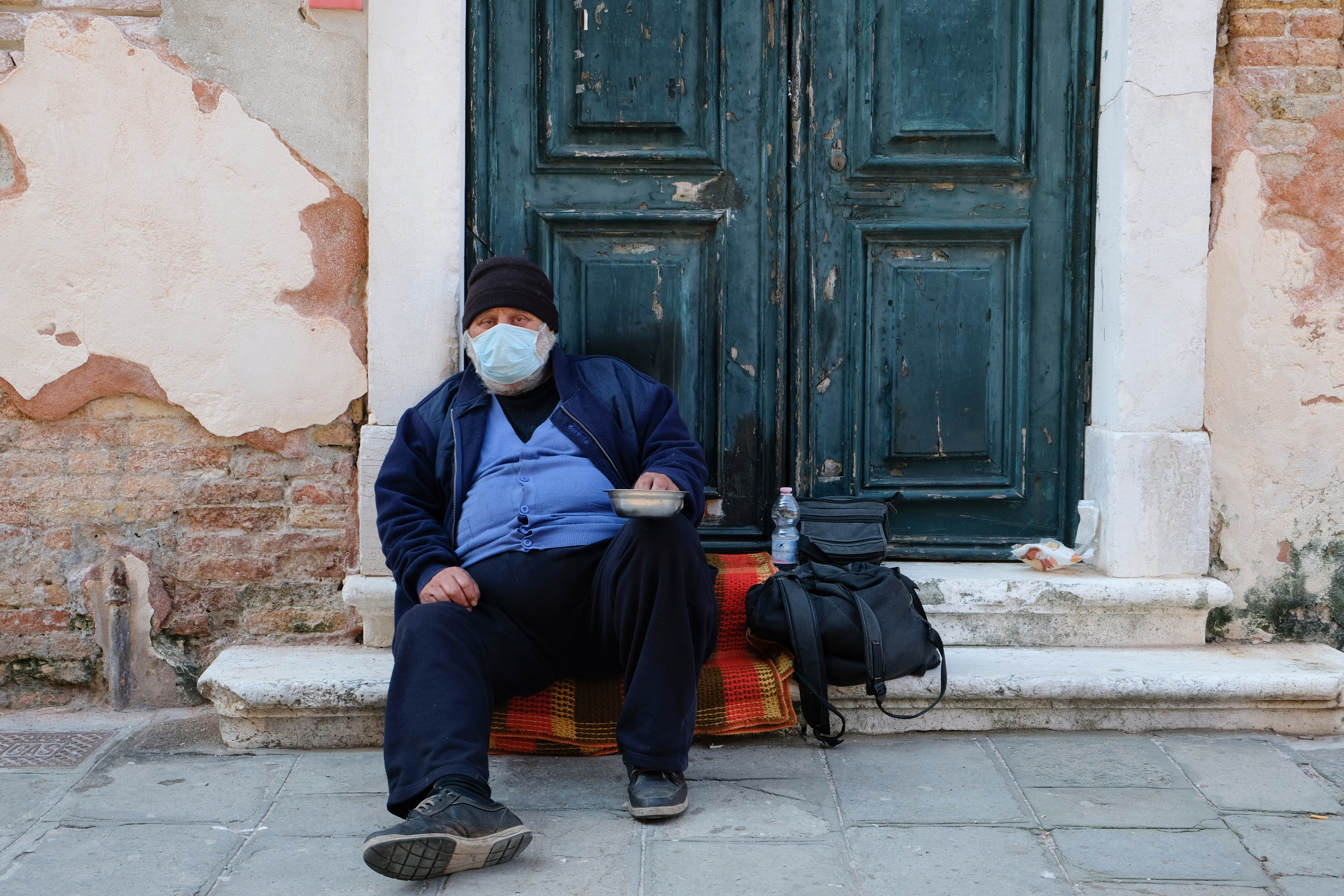 A homeless man wearing a protective mask is seen in Venice as the Italian government allows the reopening of some shops while a nationwide lockdown continues following the outbreak of the coronavirus disease (COVID-19), in Venice, Italy, April 14, 2020.