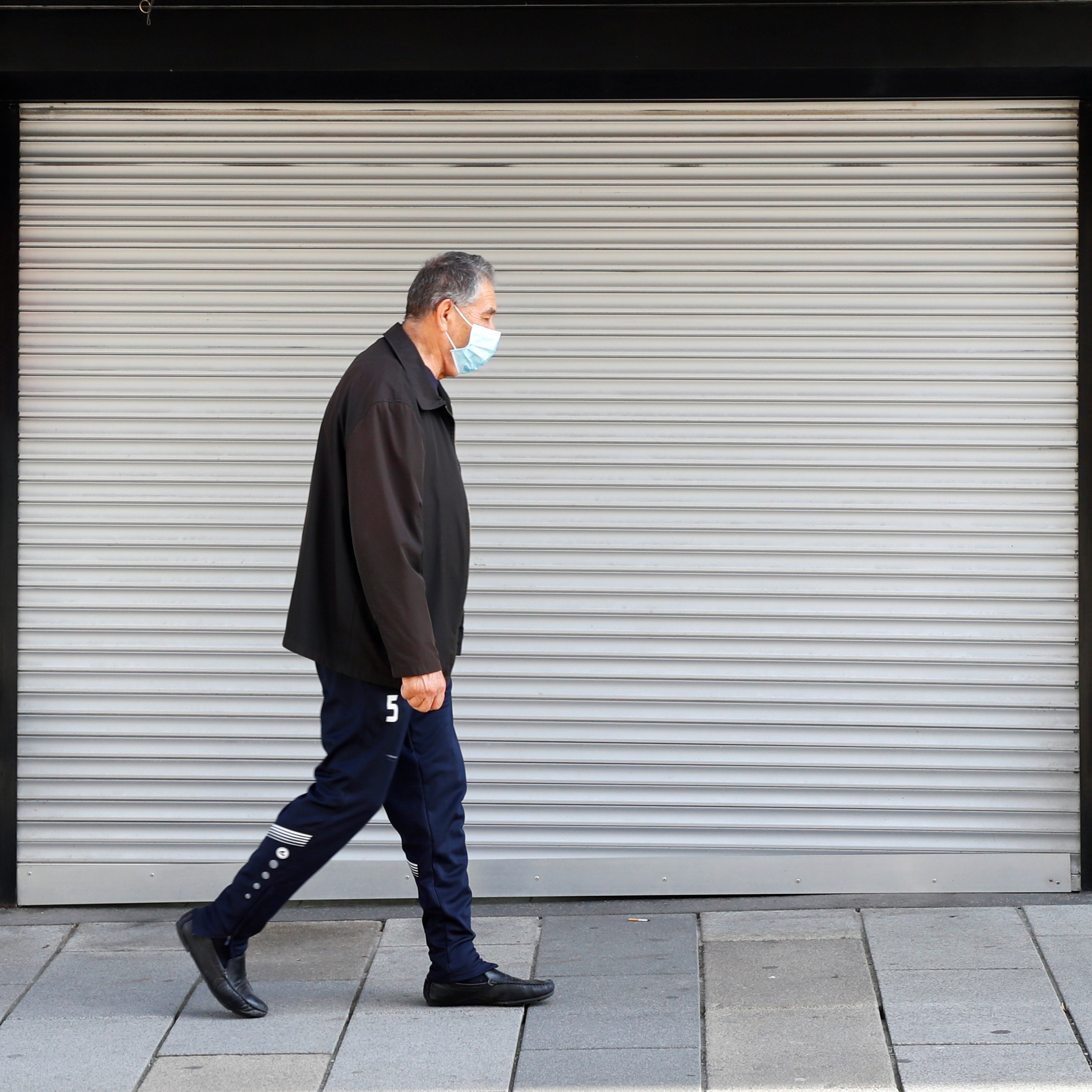 A man, wearing a protective face mask, walks past a closed shop after the Austrian government announced a lockdown including the closure of all non-essential shops, as the spread of the coronavirus disease continues, in Vienna, Austria on November 17, 2020