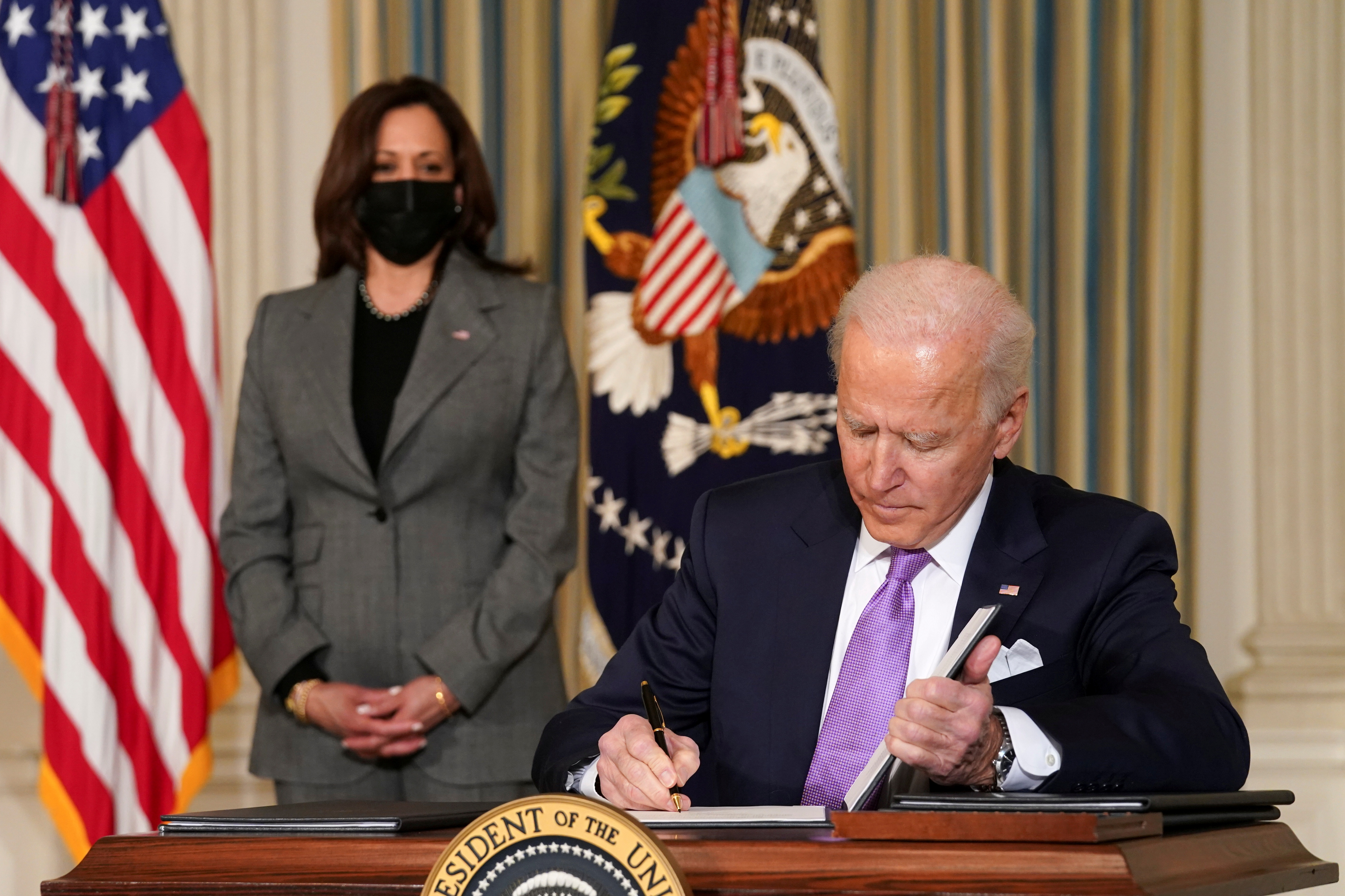 U.S. Vice President Kamala Harris watches as President Joe Biden signs executive orders on his racial equity agenda at the White House in Washington, DC on January 26, 2021.