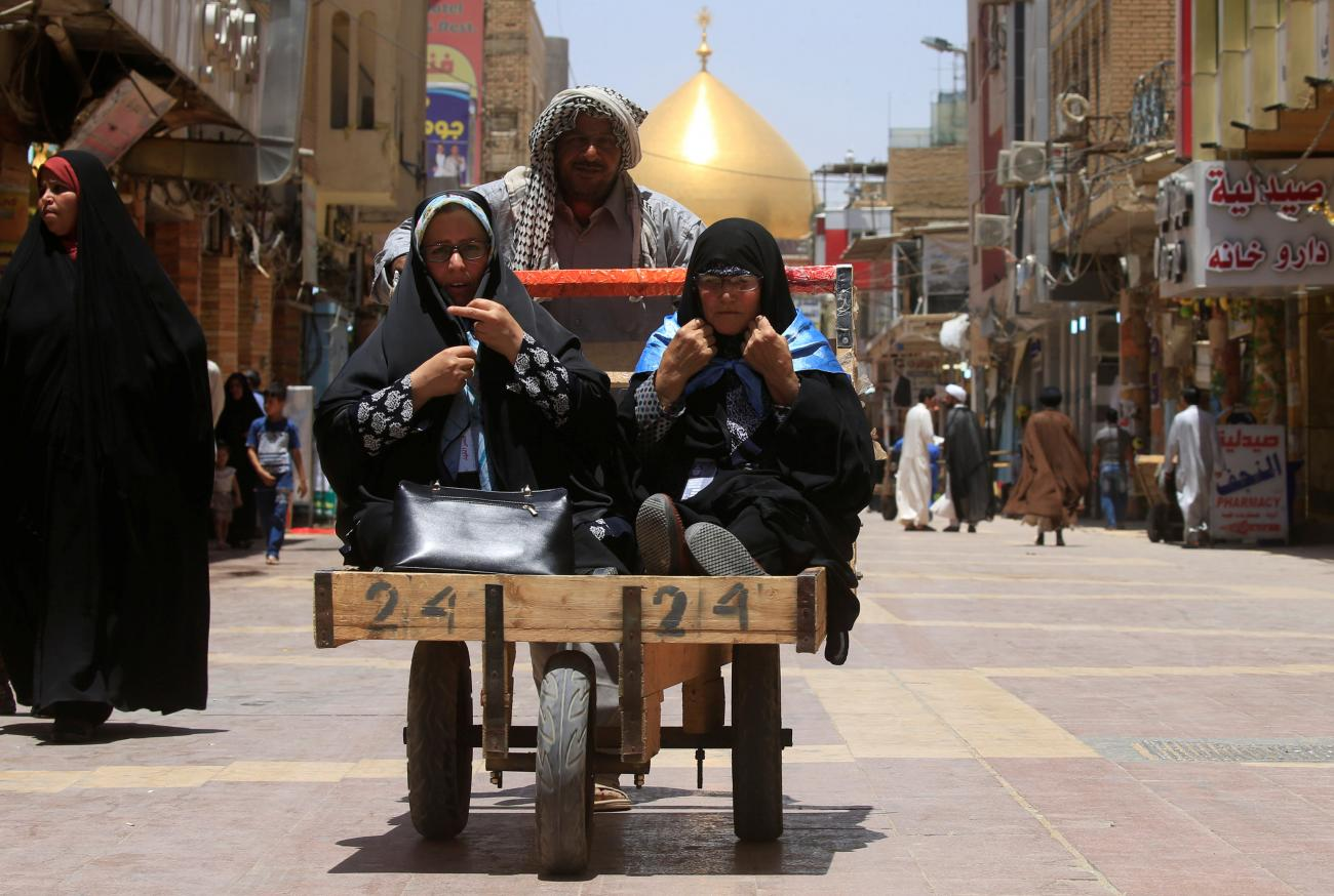 A man pushes a cart to transport women in Najaf, Iraq.