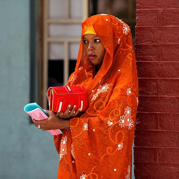 A woman waits at a polio immunization health center in Maiduguri, Borno State, Nigeria, on August 29, 2016. There is striking color in this photo. She has a bright orange scarf around her head and shoulders and leans against a brick wall that is painted dark red. She holds pink and blue copies of papers in her hands, and the light blue wall of a building can be seen in the background. She holds a bright red bag. The look on her face is serious. REUTERS/Afolabi Sotunde