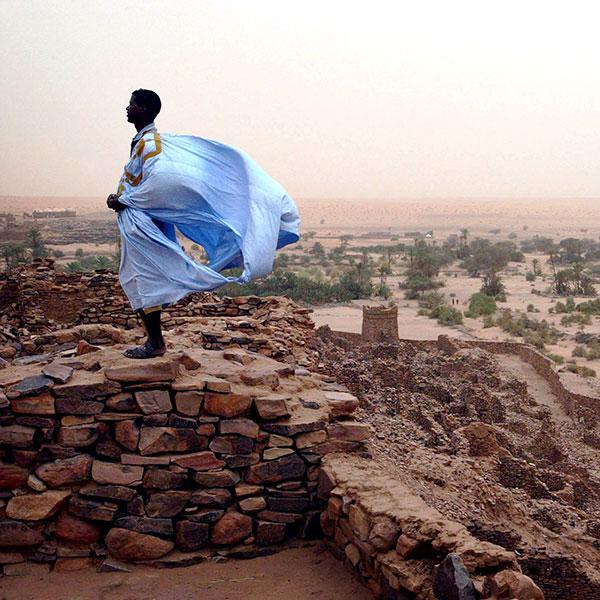 A Mauritanian man stands on what appears to be an ancient wall of old baked bricks on Aug 16, 2005 in the ancient village of Ouadane. He is wearing a light blue robe that is filling with strong winds, presumably carrying sand and dust south from the Sahara, and stands in bright contrast to the dull red background. Africa's Sahel region is threatened by desertification. REUTERS/Finbarr O'Reilly
