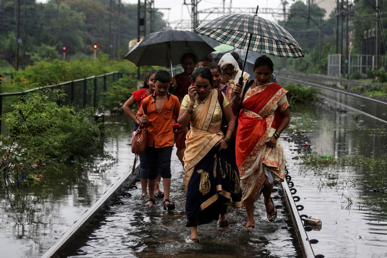 Commuters walk on waterlogged railway tracks after getting off a stalled train during heavy monsoon rains in Mumbai, India, on July 2, 2019. Several women and at least one boy are walking in a group. One of them is talking on a cell phone. Several are sharing umbrellas. The water, even on the train tracks, which are presumably slightly elevated, is up to their ankles. REUTERS/Francis Mascarenhas