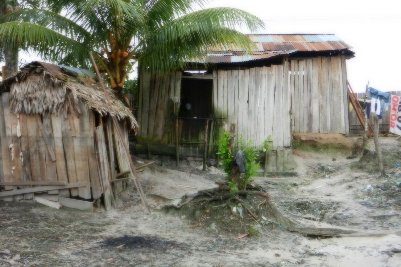 Picture shows weathered, rain-beaten buildings in the small Amazon Jungle community of Puerto Almendras, Peru