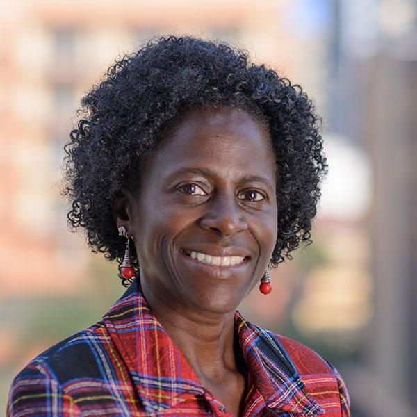 Picture shows Olive Kobusingye, Executive Director, Injury Control Center at Makerere Medical School in Kampala, Uganda. She is looking at the camera against a bright, blurred out background wearing a red-and-blue shirt in this posed shot.