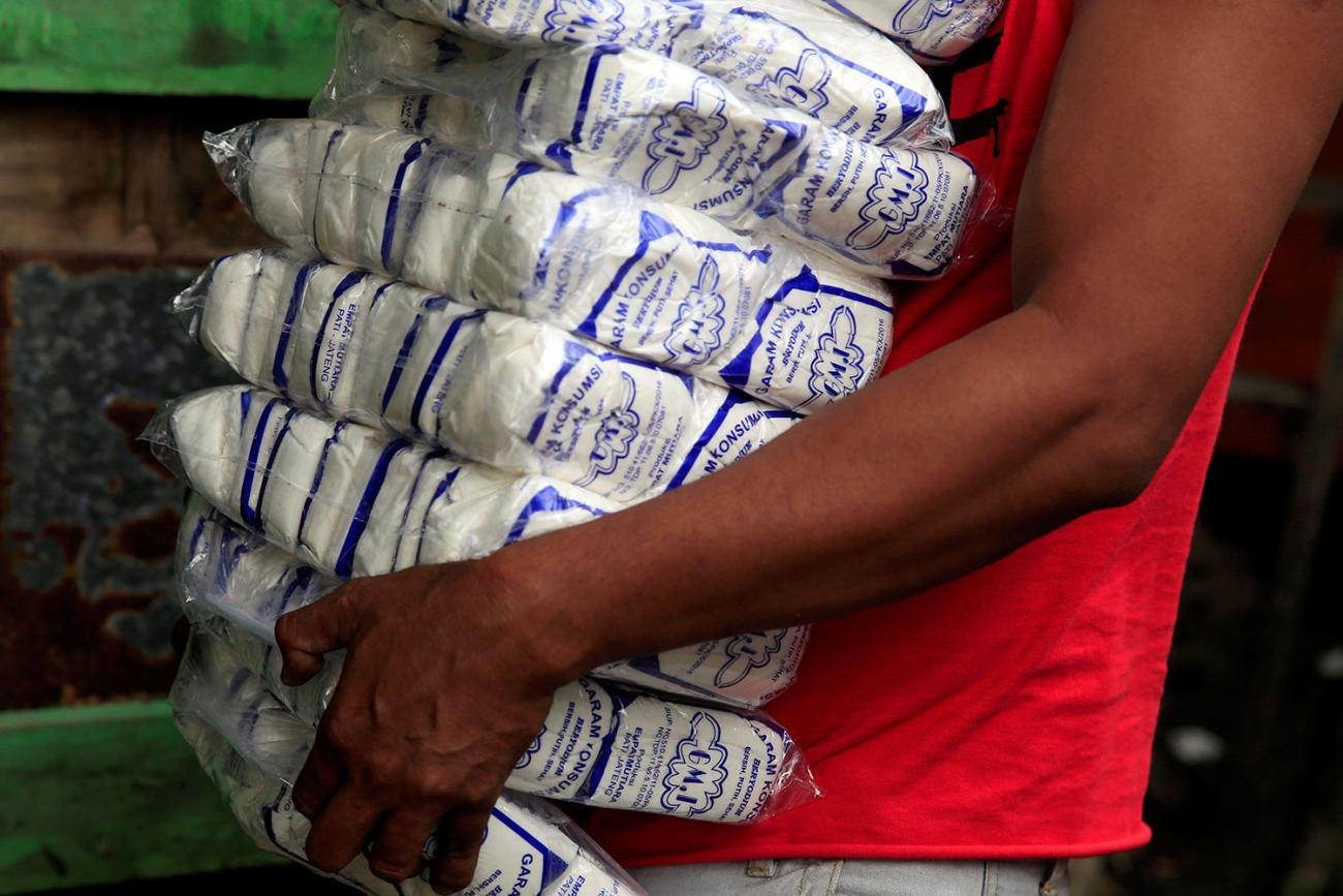 A worker carries packs of table salt at a warehouse in Jakarta, Indonesia, on March 14, 2018. Picture shows the torso of what appears to be a young man heavily burdened with more than a dozen large, one-pound bags of salt. He wears a red shirt and walks against a green backdrop and the bottom bag appears to be slipping out of his grasp. REUTERS/Beawiharta Beawiharta
