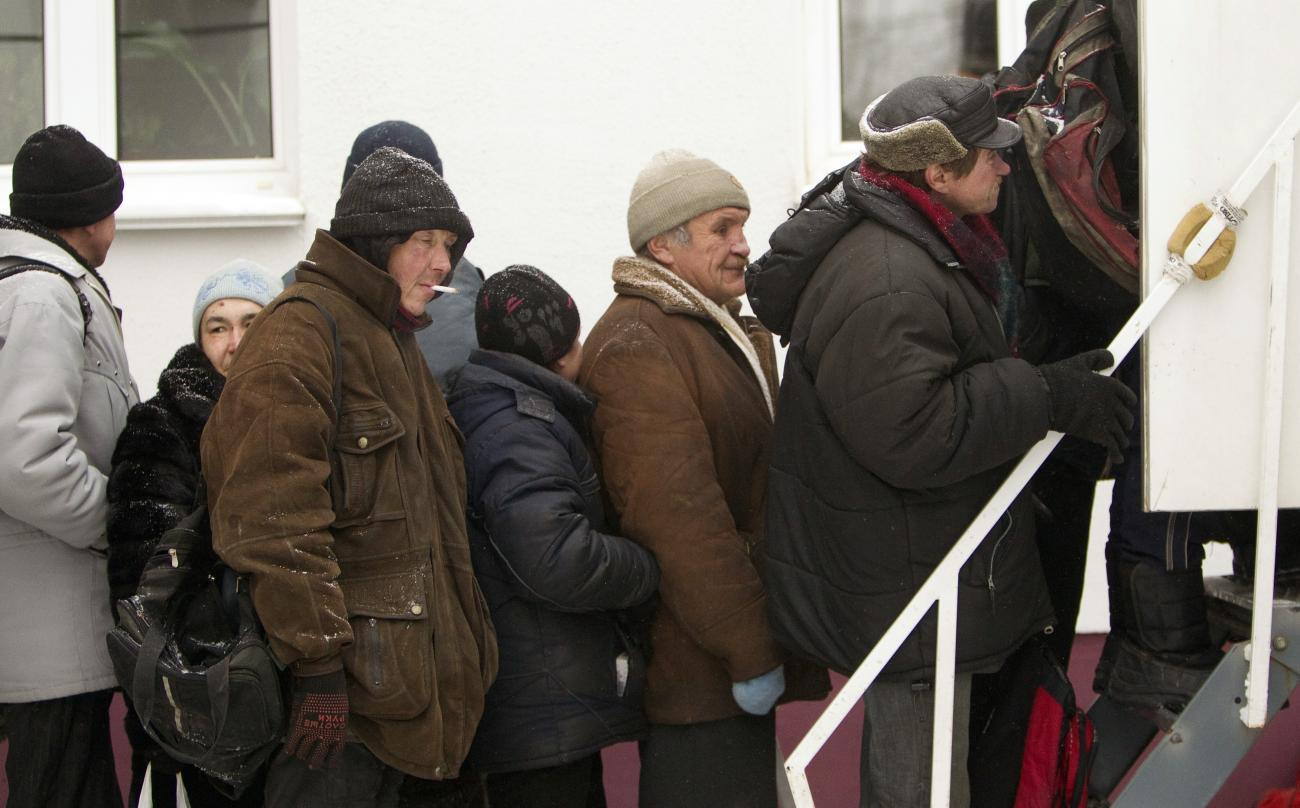 Picture shows a line of older men waiting in front of the steps of a clinic heavily bundled in winter wear against the cold.