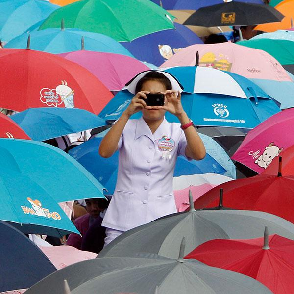 A nurse takes a photograph during a rally in front of the Government House in Bangkok October 16, 2012. Nurses attending the rally demanded better working conditions and full-time jobs, asking the government to improve job security by offering permanent contracts. The nurse stands in her white outfit against a sea of brightly colored umbrellas.