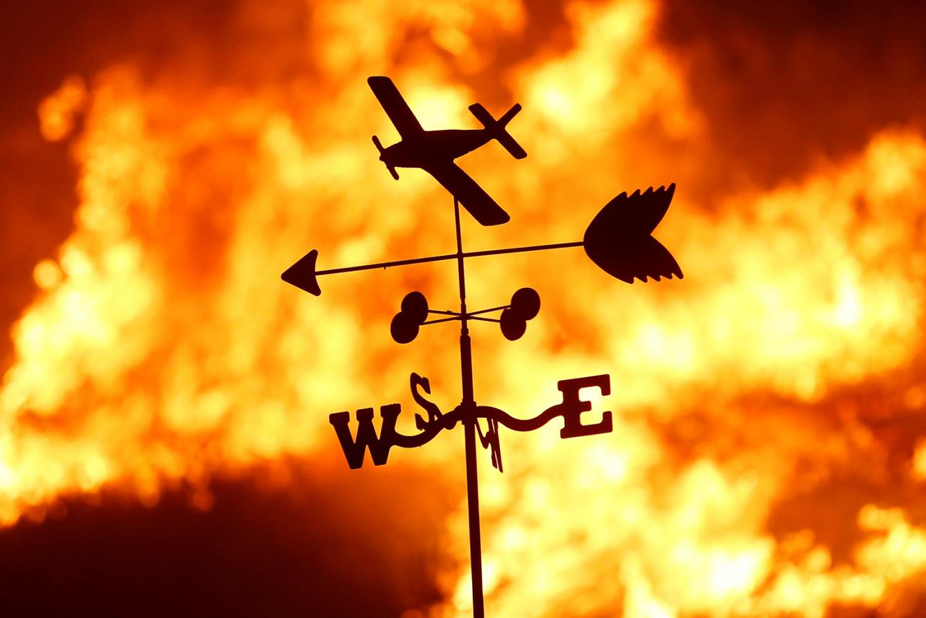 """A weather vane is pictured on a ranch during the Creek Fire in the San Fernando Valley north of Los Angeles, in Sylmar, California on December 5, 2017. Picture shows a thin metal toy-like vain with a plane, and arrow and a """"NESW"""" directional indicator silhouetted against a burning fire. REUTERS/Jonathan Alcorn"""