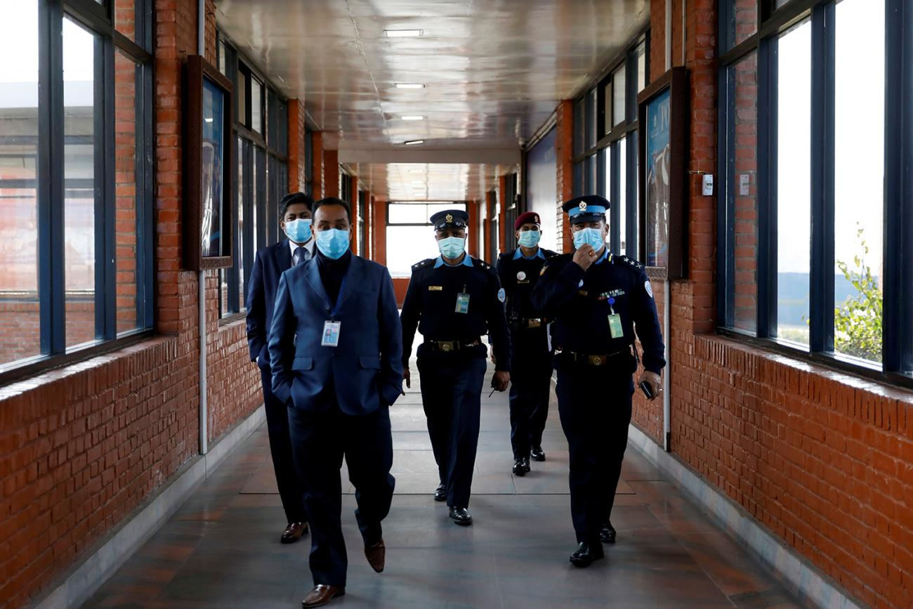 Nepalese police officers and other officials walking inside the Tribhuvan International Airport in Kathmandu after Nepal confirmed the first case of coronavirus in the country on January 28, 2020. The picture shows three officers in full uniforms and two officials wearing suits walking toward the camera down a long air terminal corridor with windows on both sides. REUTERS/Navesh Chitrakar.