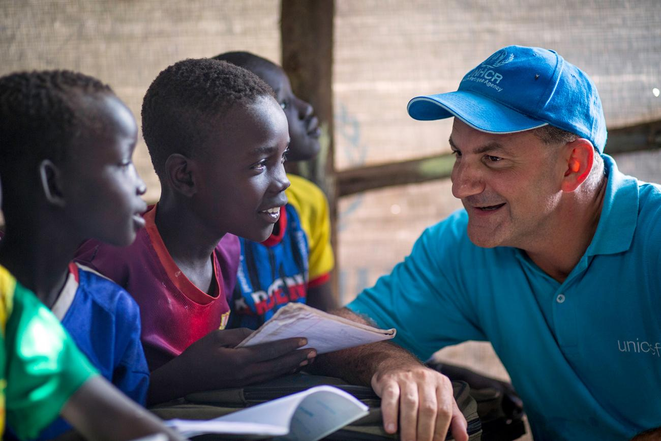 Peter Salama visits a makeshift school at Kule Camp in the Gambella region of Ethiopia on August 12, 2014, when he was the Country Representative of UNICEF Ethiopia. Picture shows Dr. Salama wearing a blue hat talking to several boys in a classroom. They are all smiling. UNICEF/Jiro Ose/UNI170605