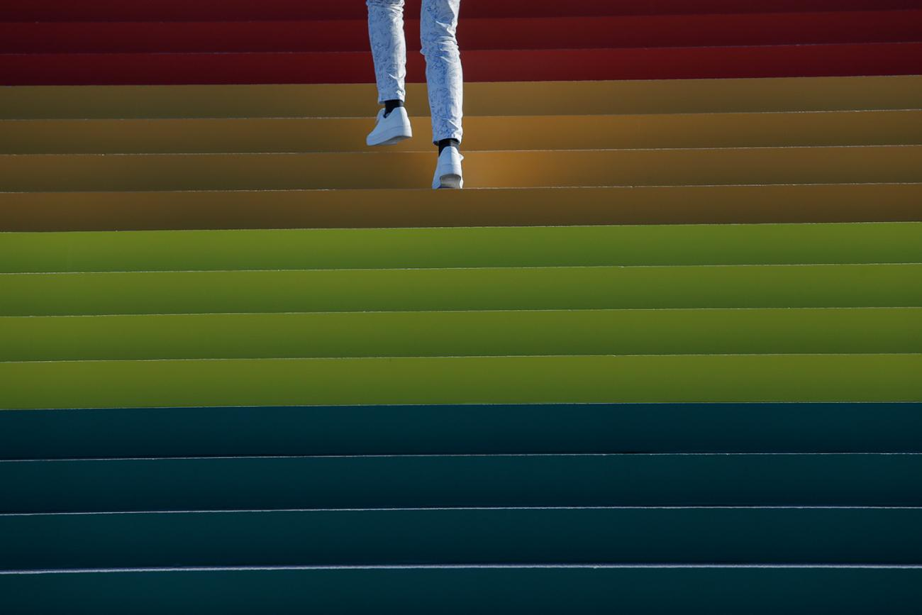A person walks up a giant LGBTQ+ Pride Flag installed on the steps of Franklin D. Roosevelt Four Freedoms State Park to celebrate World Pride in New York City on June 14, 2019. Photo shows the legs and feet of someone wearing white pants and white sneakers walking up a wide staircase that fills the frame and is brightly adorned in rainbow hues. This is a striking photo. REUTERS/Andrew Kelly