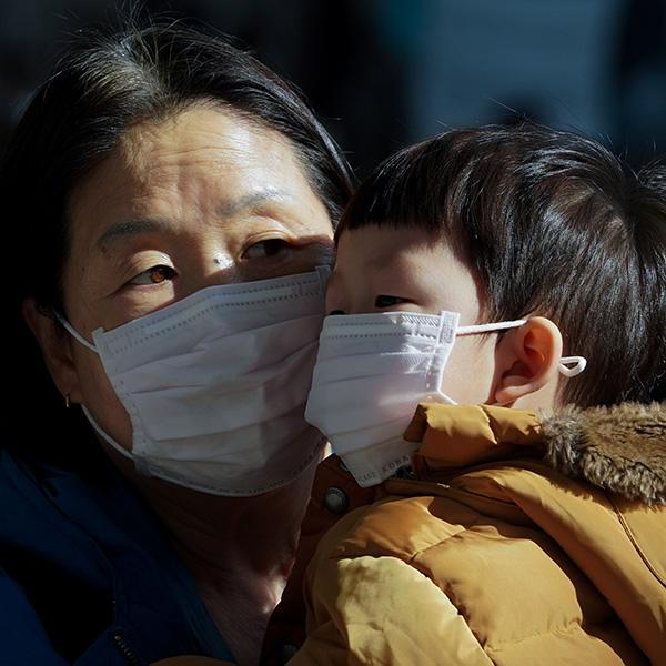 A mother and her child wear a mask to prevent contacting a new coronavirus in Seoul, South Korea, January 26, 2020. The photo shows the two face to face with each other, but their faces are covered almost completely below their eyes by the dust masks. REUTERS/Yonhap