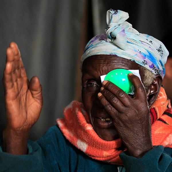 A woman at a clinic in Olenguruone, Kenya on Oct. 29, 2013 undergoes an eye exam, cataract check, and retinal scan with a technology using smartphones that uploads the data to a doctor for analysis. The photo shows a mature woman wearing a bright orange scarf taking an eye test, holding a green patch to her left eye and raising her right hand in front of her face. REUTERS/Noor Khamis