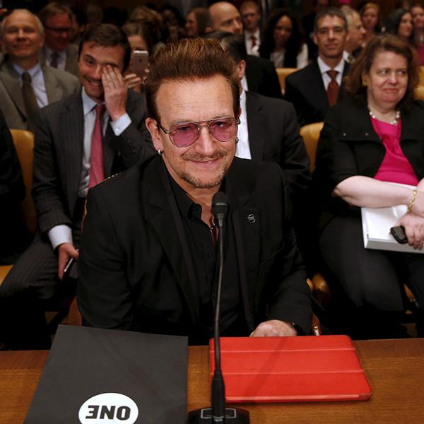Famous singer and social activist Bono attends a Senate Appropriations State, Foreign Operations and Related Programs Subcommittee hearing on foreign assistance in Washington D.C. on April 12, 2016. The photo shows Bono at a long table with several rows of chairs behind him. The chairs are filled with people who appear to be laughing. The REUTERS/Yuri Gripas