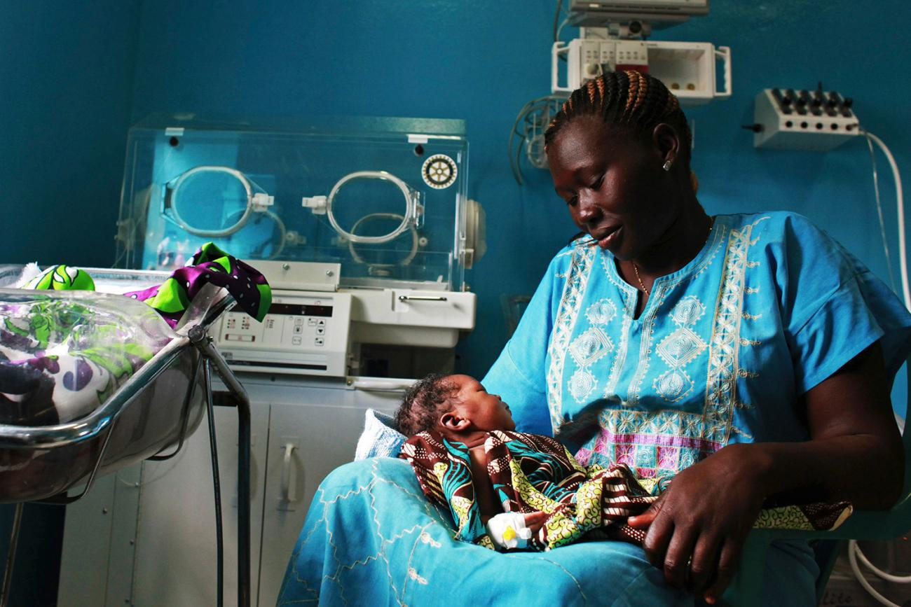 A woman holds her newborn in a nursery at the Juba Teaching Hospital in South Sudan on Apr 3, 2013, which had one of the world's highest maternal mortality rates then at 2,054 per 100,000 live births. Photo shows a woman looking adoringly on her baby, who rests in her lap. REUTERS/Andreea Campeanu