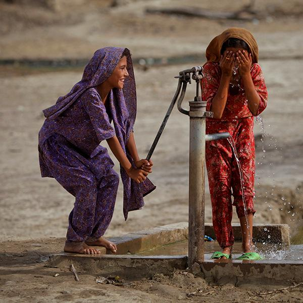 A hand pump provides access to water in the village of Lal Bux Lund in Pakistan's Sindh province on July 8, 2011, but 1 in 4 health facilities around the world lack basic water services. The picture shows two girls, one pumping, the other washing, and both laughing. REUTERS/Akhtar Soomro