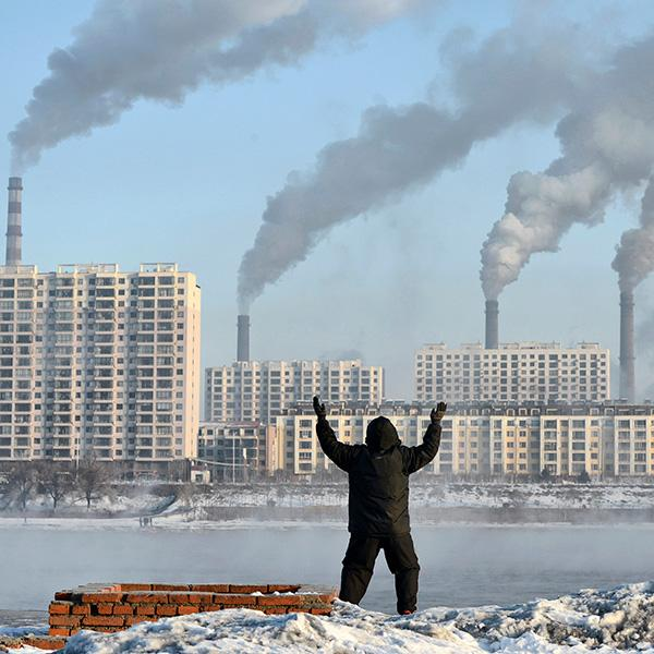 Factories emit smoke in Jilin province, China, across the Songhua River from where an elderly man exercises on the morning of Feb 24, 2013, after Chinese authorities announced plans to curb pollution. The photo shows the man in the foreground, back to the camera, with buildings on the other side of the river pouring out smoke. REUTERS/Stringer