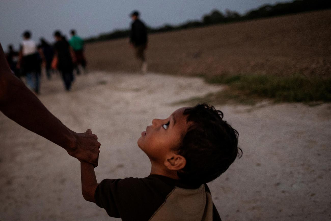 A 3-year-old boy named Eduardo holding father Luis's hand on Nov. 7, 2018. Both are from Central America, where progress toward reducing stunting in children under 5 has been particularly noticeable. Picture shows Eduardo looking up pensively at his father at they walk along a road in what appears to be dusk or pre-dawn dim light. Luis is off-camera and only his arm visible. REUTERS/Adrees Latif