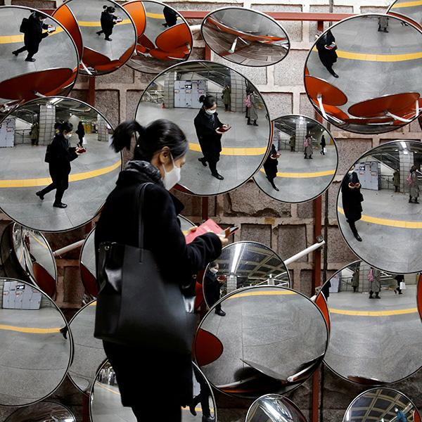A woman wearing a mask to prevent the coronavirus is reflected in mirrors in Seoul, South Korea on February 24, 2020. This is an amazing image of a woman walking by a display of spherical mirrors, the sort of which someone might place on a corner to see a wide angle. She is wearing a black face mask and is reflected in all the mirrors. REUTERS/Heo Ran