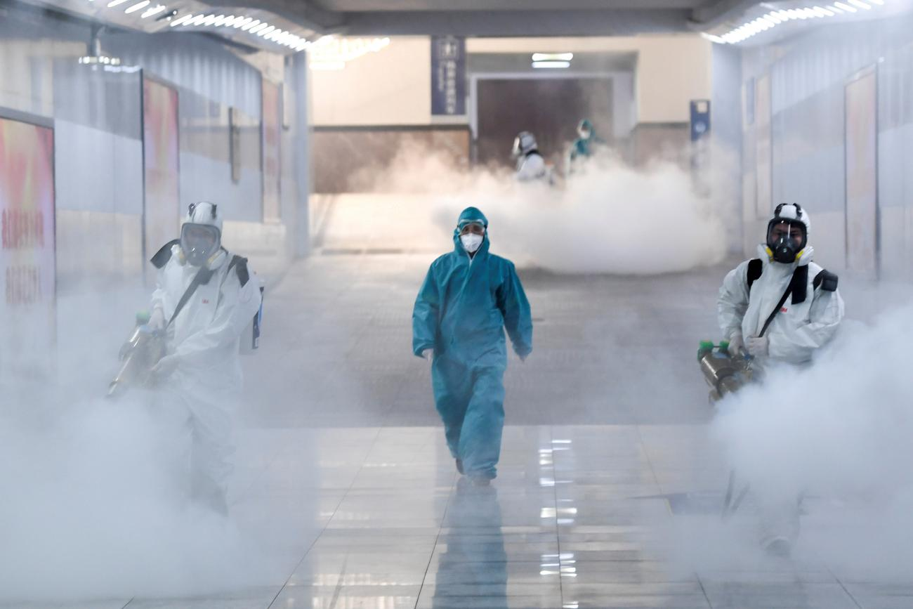 Volunteers in protective suits disinfect a railway station in Changsha, Hunan province, China, February 4. The photo shows several people clad head-to-toe in protective suits fogging what is presumably a disinfectant in thick clouds. REUTERS/cnsphoto