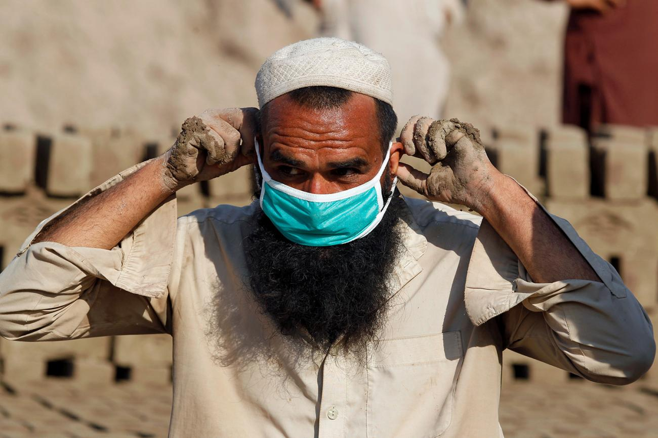 The picture shows a man whose hands are muddy from physical labor donning a blue surgical mask over his face and long beard.