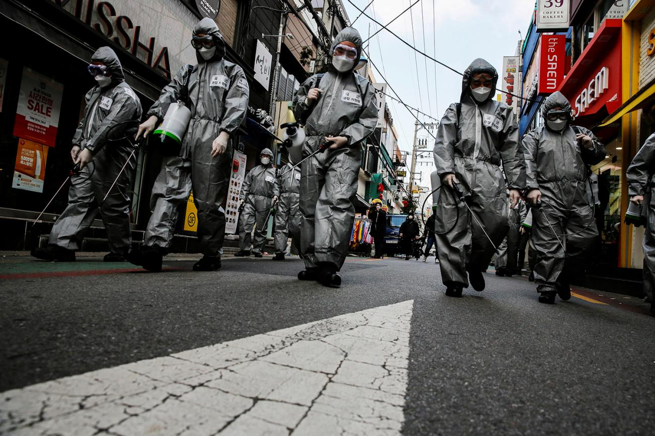 South Korean soldiers in protective gear sanitize a shopping street in Seoul, South Korea on March 4, 2020. The image is striking showing the soldiers dressed in silver space-suit looking protective gear walking down a more or less abandoned street in what appears to be a normally busy shopping district. REUTERS/Heo Ran