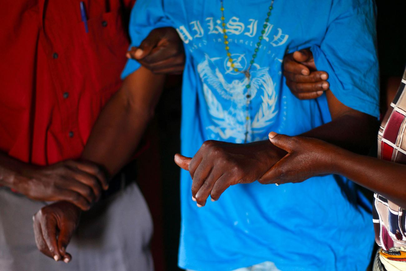 A person with HIV/AIDS is helped to his bedroom by caregivers from a community home-based care team visiting him at his home in Matero township on the outskirts of Lusaka, Zambia on April 17, 2012. The picture shows the torso of a man wearing a loose-fitting light blue shirt being helped by two other people. REUTERS/Darrin Zammit Lupi