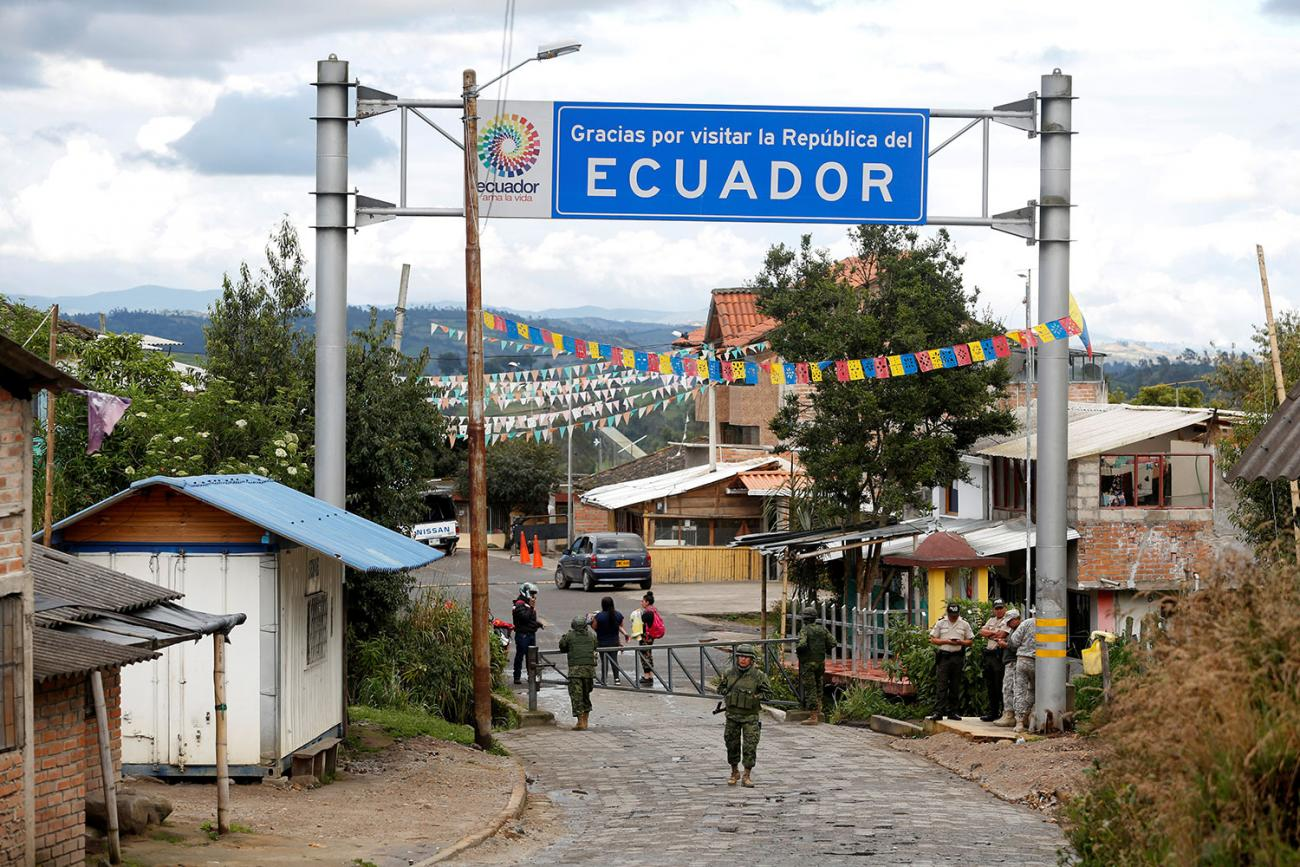 """Soldiers guard the Ecuadoran side of a border with Colombia in Tufino, Ecuador on March 15, 2020, after country leaders announced the closure of its borders to all foreign travelers due to COVID-19. The photo shows a simple border crossing through a small town with a big sign reading """"Ecuador"""" above the street. The crossing is closed with metal barricades, and a soldier stands out front. REUTERS/Daniel Tapia"""