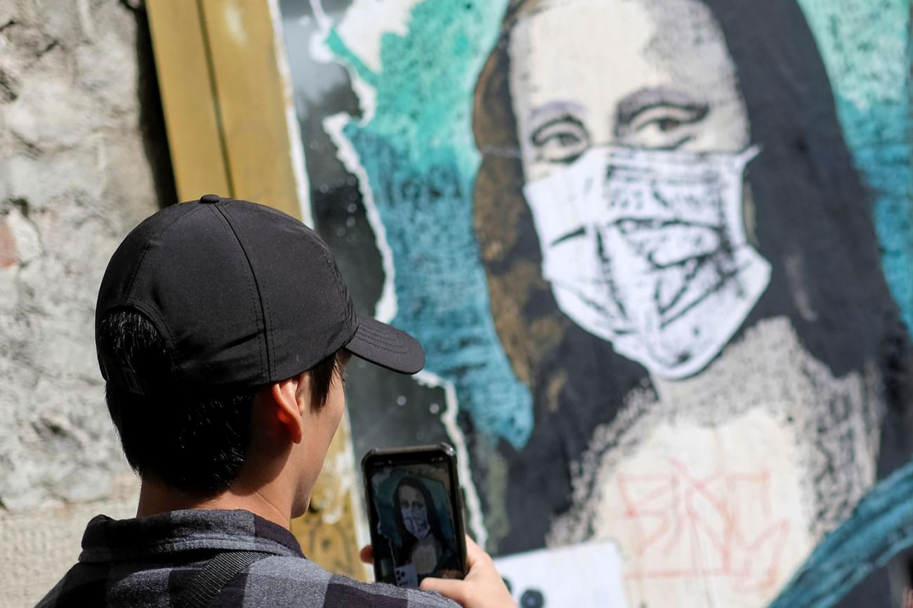 A tourist takes a picture of an image of Mona Lisa with a protective face mask after further cases of coronavirus were confirmed in Barcelona, Spain on March 6, 2020. The photo shows a man with dark hair and a black cap taking a cell phone photo of a likeness of Da Vinci's most famous painting with Mona wearing a mask. REUTERS/Nacho Doce