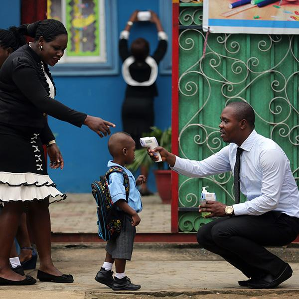 Picture shows a young boy carrying a backpack and wearing a school uniform standing in front of a brightly-colored building. A well-dressed woman directs him while a well-dressed man kneels and points a high-tech thermometer at his head to take his temperature.