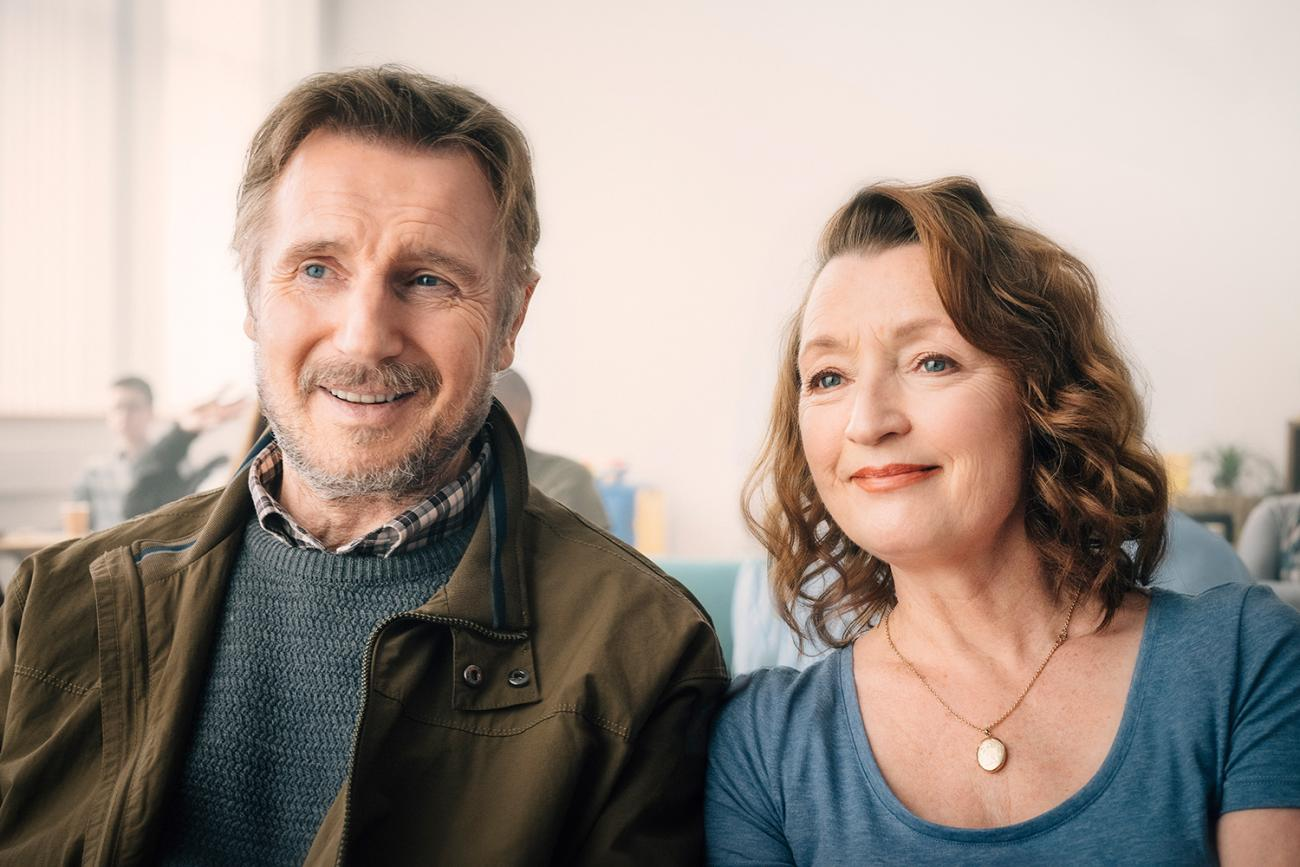 Liam Neeson and Lesley Manville give outstanding performances in the new film ORDINARY LOVE, from Bleecker Street, and they are helped by a powerful, semi-autobiographical script by Owen McCafferty. Image is of the two actors sitting together and smiling in a hospital waiting room. Credit: Aidan Monaghan/Bleecker Street