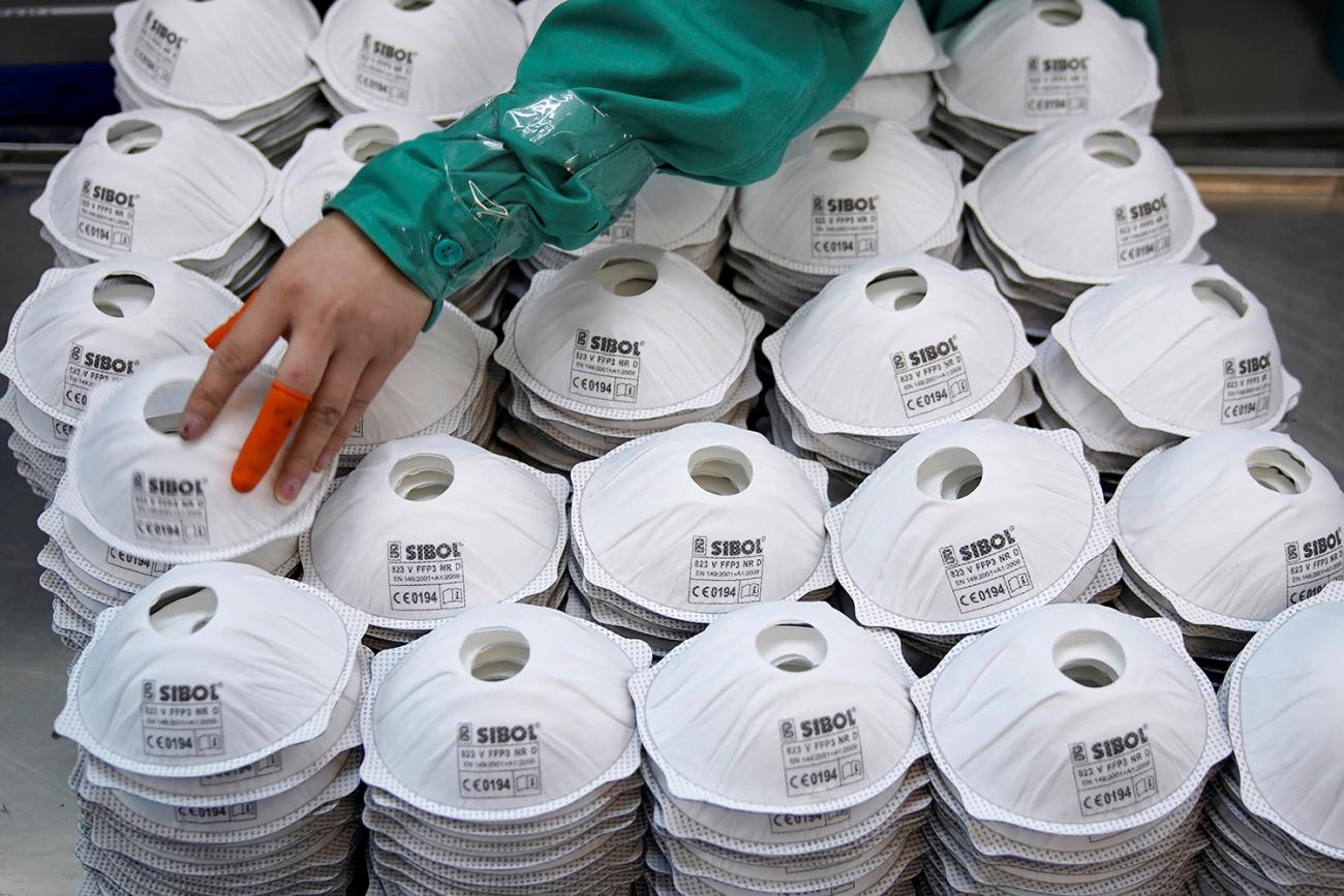 Masks are seen on a production line manufacturing masks at a factory in Shanghai, China January 31, 2020. New York City alone could face a shortage of millions of masks in the coming months. The image shows a human hand with two bright orange bandaids on the thumb and middle finger picking its way across a huge pile of masks. REUTERS/Aly Song