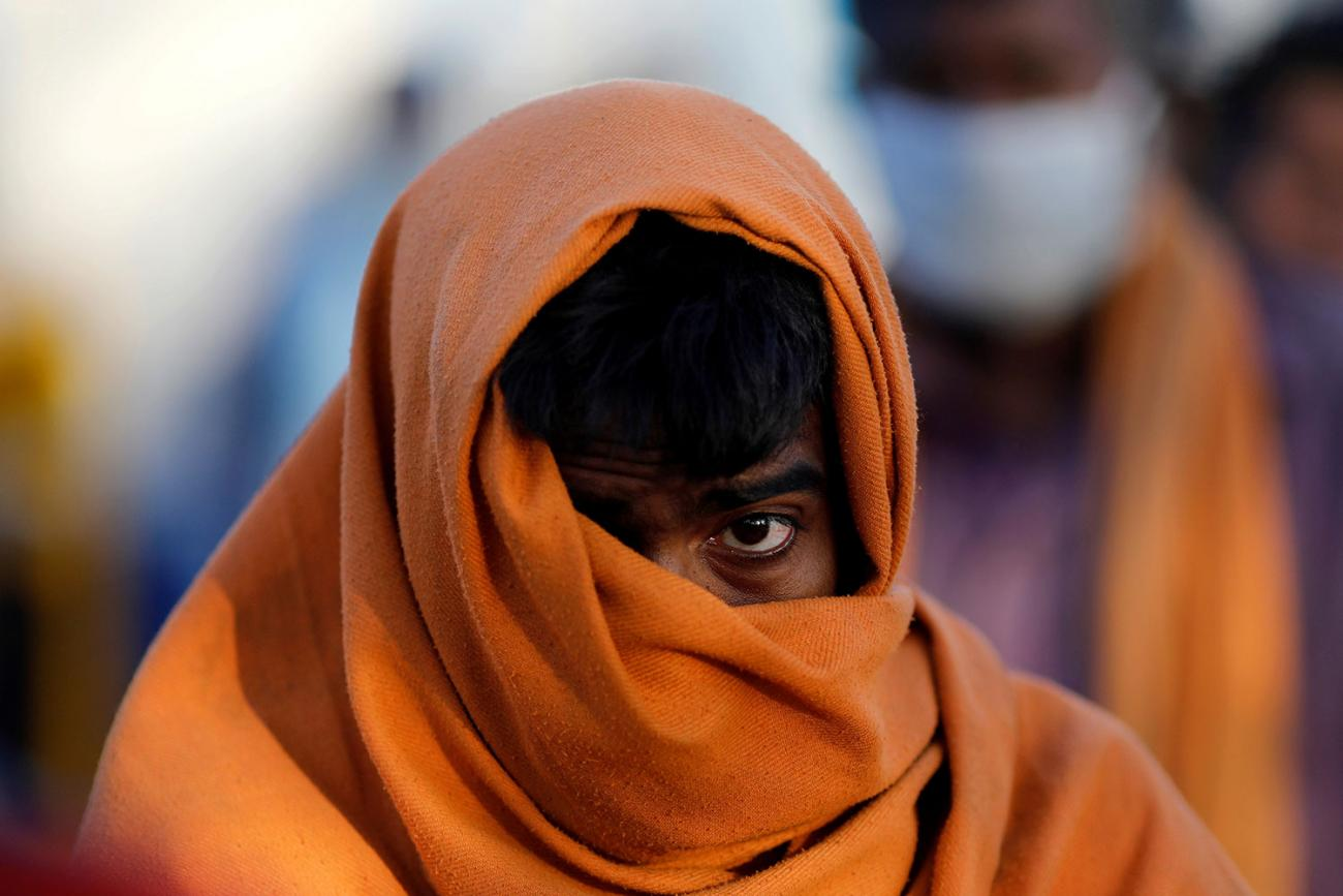 A homeless man stands in a queue as he waits for food during a 21-day nationwide lockdown to slow the spreading of the coronavirus disease (COVID-19) in New Delhi, India on April 3, 2020. The image is very striking showing the man with a large wrap around his head and mouth against a creamy, out of focus, colorful background. REUTERS/Adnan Abidi