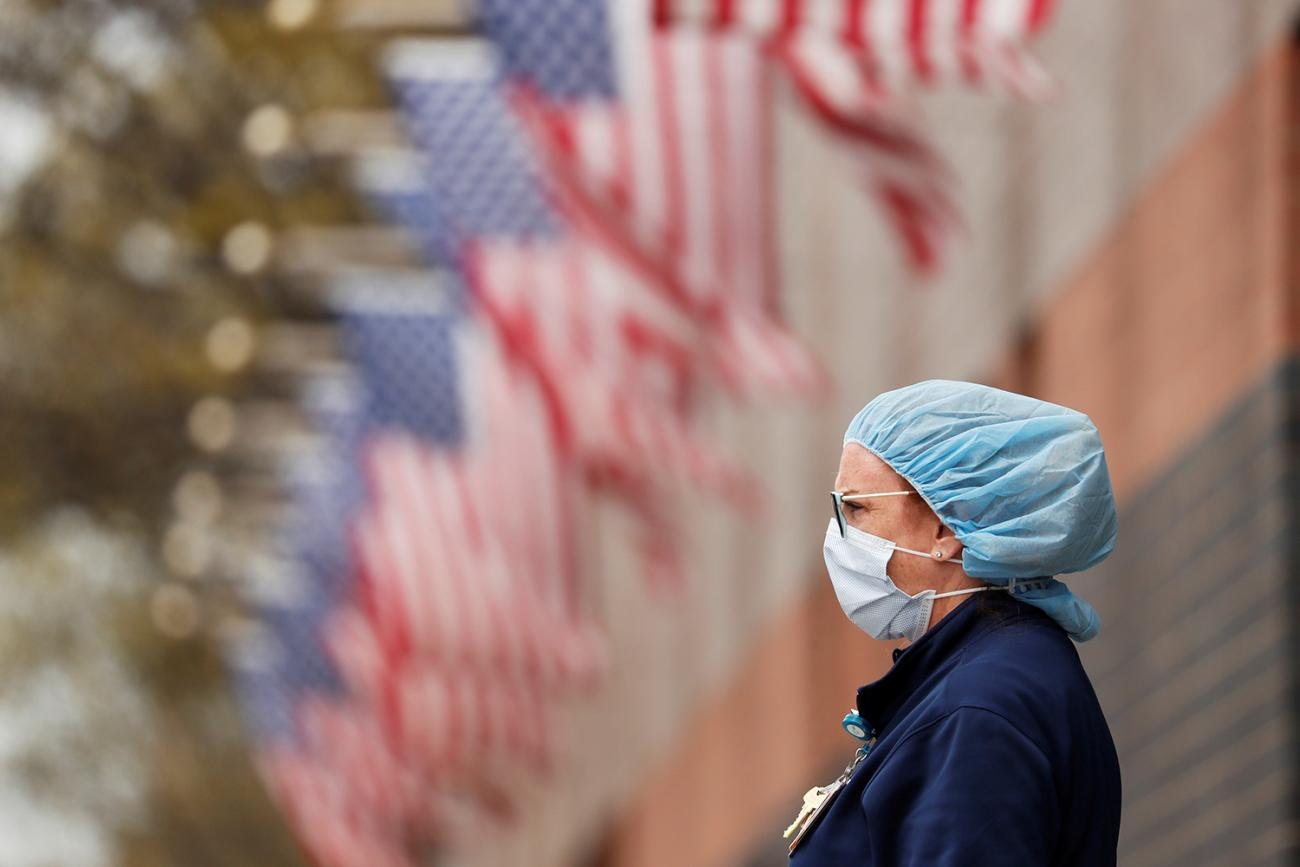 The photo shows a nurse wearing personal protective equipment leaning against a fence that is topped by many American flags.