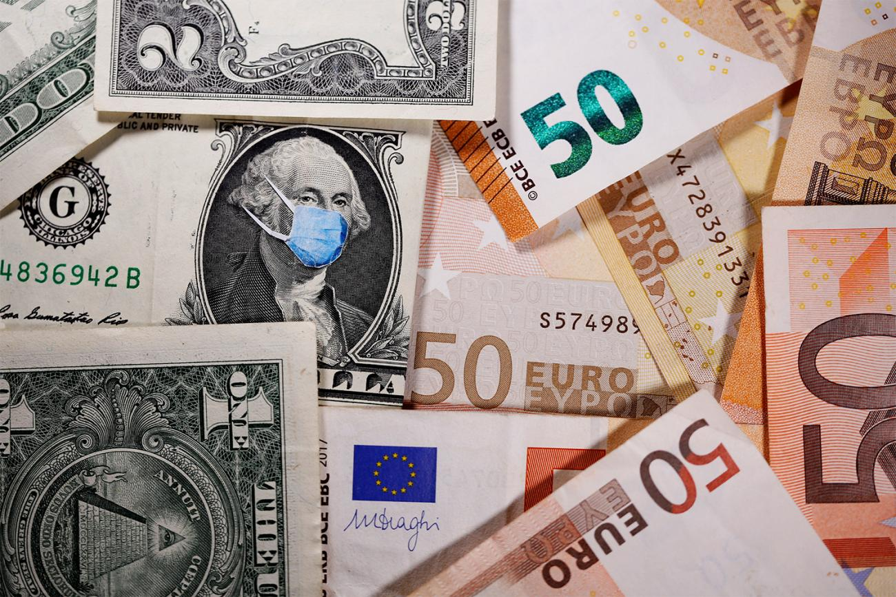 George Washington is seen with a printed medical mask on the one-dollar bill near fifty-Euro banknotes in this illustration created during the coronavirus pandemic on March 31, 2020. The photo shows a bunch of paper money, dollars and euros, with a blue surgical-style mask on one of the bills. REUTERS/Dado Ruvic