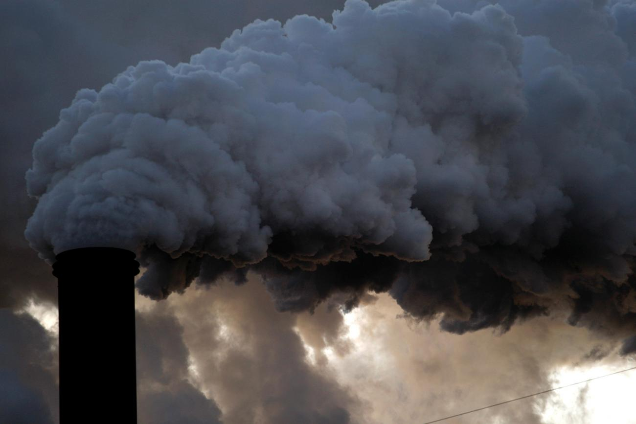 A boiler stack at the Sugar Cane Growers cooperative in Belle Glade, Florida on January 6, 2010. The image shows a large smokestack belching out black billows and blocking the cloudy sky.