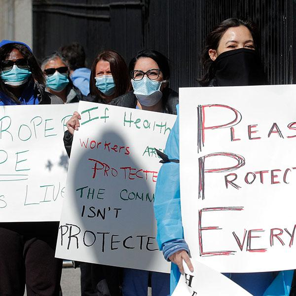 """Nurses at Montefiore Medical Center in New York City's Bronx borough hold a protest demanding N95 masks and other critical personal protective equipment during the COVID-19 pandemic on April 2, 2020. The photo shows a number of nurses lined up holding placards. One of them plays off the term PPE and spells out """"Please Protect Everyone."""" REUTERS/Brendan Mcdermid"""