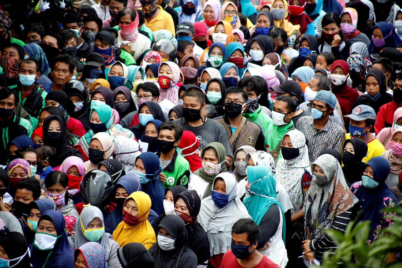 Indonesians queue to get free food without social distancing amid the coronavirus disease (COVID-19) outbreak in Bogor, Indonesia, on April 20, 2020. The photo shows a crush of people, many of them wearing face masks, crowded in all parts of the shot's frame. REUTERS/Antara Foto/Yulius Satria Wijaya